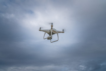 Flying drone with cloudy sky background controlled by professional photographer