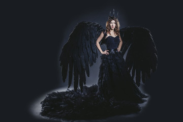 Female demon with black wings costume in carnival and religious