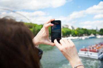 Girl making photo of city using smart phone