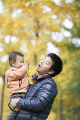 Happy real father and son playing in front of ginkgo trees