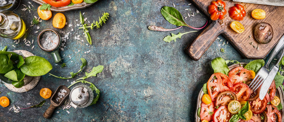 Healthy vegetarian salad making preparation with tomatoes on rustic background, top view, banner, copy space