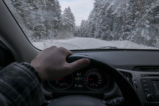 Driver's point of view looking through car windshield of snowy road, winter driving, forest trees covered with snow