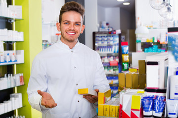 Male pharmacist wearing white coat standing  in drug store