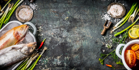 Food rustic background for healthy or diet cooking recipes with raw fishes, seasoning,vegetables and spices ingredients, top view, place for text, banner