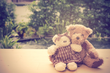 Lovely couple teddy bears sit with big hug on wooden floor with
