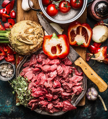 Raw gut meat with kitchen knife  fresh vegetables, seasoning and spices for tasty cooking on dark rustic background, top view