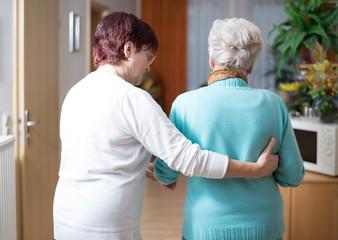 ältere Dame wird von Pflegerin gestützt