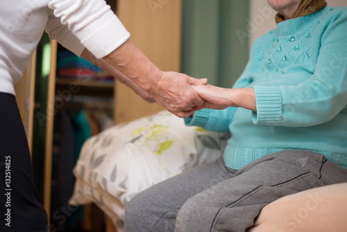 alte Frau sitzt auf dem Bett und bekommt Hände zum