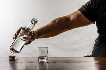 ein Mann sitzt an einem Tisch und gießt sich Schnaps in ein Glas