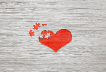 Red wooden puzzle heart on grey background