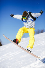 Jumping snowboarder on blue sky background