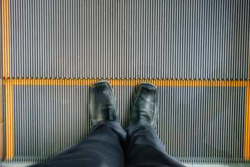 Man Standing and Selfie feet in black leather shoes on escalator steps, top view