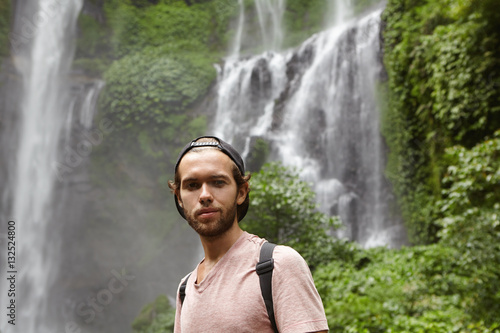 1694dba1c2c Close up portrait of handsome man wearing baseball cap backwards relaxing  outdoors