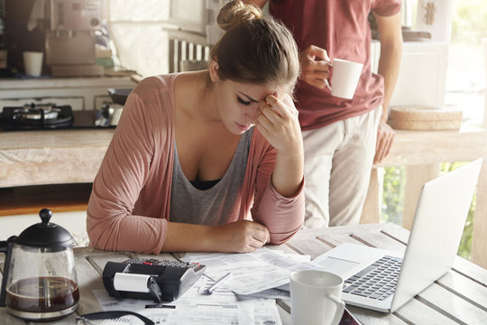 Thoughtful stressed young female sitting at kitchen table with papers and laptop computer trying to work through pile of bills, frustrated by amount of domestic expenses while doing family budget