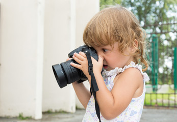 Baby with a photo camera takes pictures.