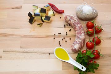 Salsiccia con ortaggi ,spezie e condimenti su tavola di legno