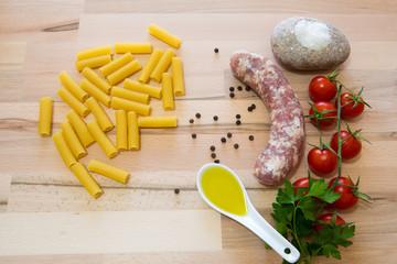 Salsiccia e pasta cruda con varie spezzi e ortaggi su tavolo di legno