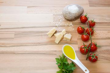 Pomodori formaggio grana sale olio per una buonissima preparazione del sugo su tavolo di legno