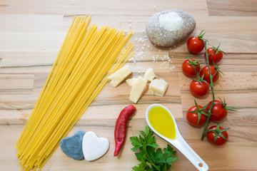 Pomodori formaggio grana sale olio per una buonissima preparazione del sugo con la pasta su tavolo di legno