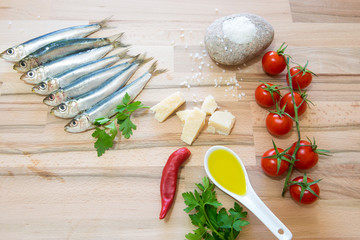 Sardine con varie spezzi e ortaggi su tavolo di legno