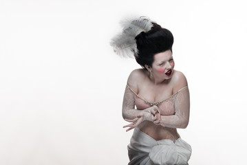 emotional actress brunette woman in a transparent lace dress and lush hair with white feathers on a white background in studio