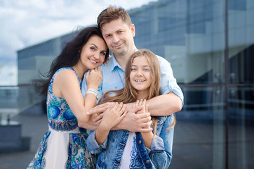 Portrait of happy young family while walking. Mom, Dad and kid laughing and hugging, enjoying nature outside. Sunny day. ?lose-up. close