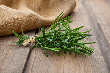 Rosemary bound on a wooden background.
