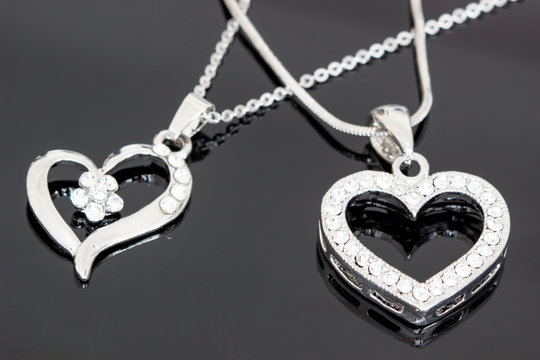 silver jewelry / necklaces with heart pendants on black background / necklaces with heart pendants for woman