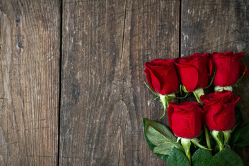 Old wooden background with red roses copy space.