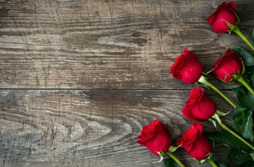 Bouquet of red roses on old wooden background.