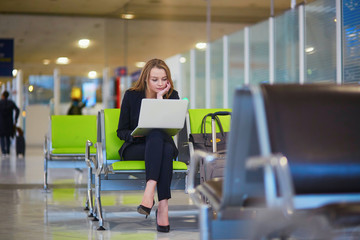 Woman in international airport terminal, working on her laptop