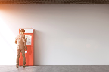 Rear view of man near a red ATM machine