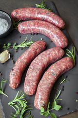Raw Sausages with Herbs and Spices on Slate