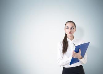woman with clipboard near blue wall