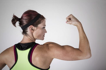 Beautiful strong muscular woman flexing her biceps and arm muscles. View from behind to show her ripped back and arms. Female Body builder