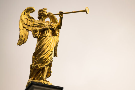 Golden angel with a trumpet and copy space.