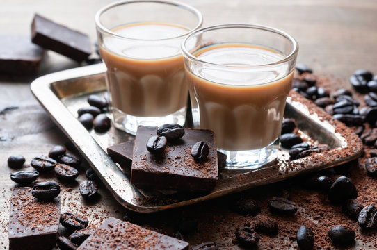 Coffee liqueur, shot glasses with homemade baileys, roasted coffee beans, chocolate, selective focus