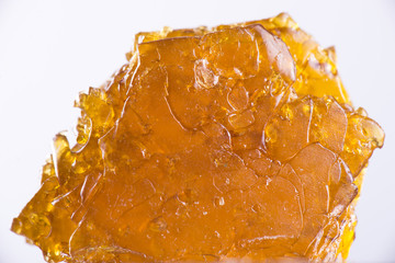 Cannabis oil concentrate aka shatter isolated over white backgro