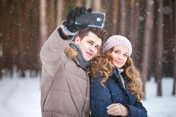 people,season,love,technology and leisure concept - happy couple taking picture with smart phone self ie stick on over winter background