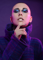 Young fashion model posing in studio. Bald. Bright make up.