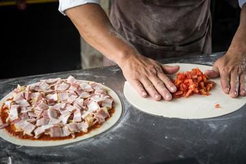 Hands preparing a pizza  (dark background)