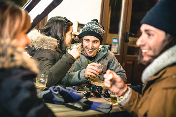 Happy friends drinking beer and eating chips after ski - Friendship concept with cheerful people having fun at bar restaurant resort with snow equipment - High iso image with shallow depth of field