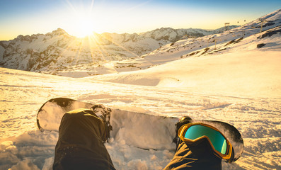 Snowboarder sitting on relax moment at sunset in french alps ski resort - Winter sport concept with person on top of the mountain ready to ride down - Legs view point with warm backlighting filter