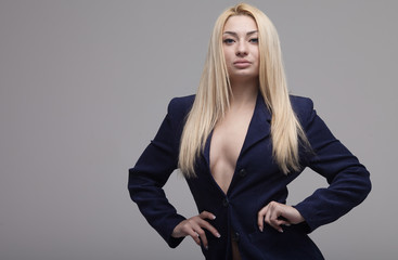 Sexy blonde business lady wearing blue suit .big lips and boobs.