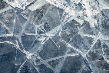 Texture of ice surface, cracked ice floating on blue water, seasonal winter landscape.