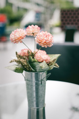 artificial flowers made from cloth with steel jug ont the glass table