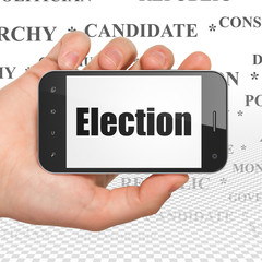 Political concept: Hand Holding Smartphone with Election on display
