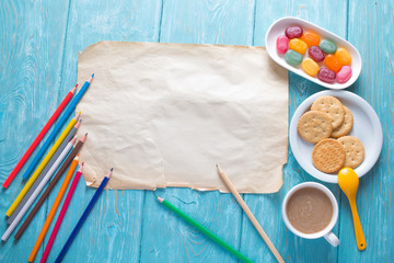 White sheet of paper. Blue vintage background. Colour pencils. Multi-colored candies and crackers on a plate and a cup of coffee with milk.