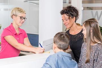 Mutter mit Kindern bekommt einen neuen Zahnarzttermin