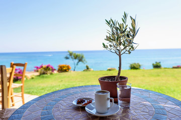 Traditional cup of coffee on a table with olive tree, glass of water and jam, with the sea view and sky in protaras, cyprus island.